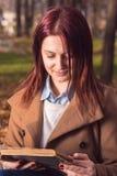Rothaarigemädchen, das ein Buch im Park liest Stockbilder