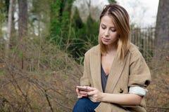 Rothaarigemädchen, das eine Mitteilung unter Verwendung des Handys schreibt Stockfotografie