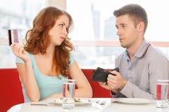 Rothaarigemädchen, das für das Mittagessen anstelle des Mannes zahlt stockfotografie