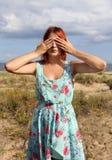 Rothaarigemädchen, das ihre Augen mit den Händen an der Küste bedeckt stockbilder