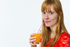 Rothaarigemädchen, das Orangensaft trinkt Lizenzfreie Stockfotos