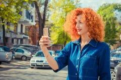 Rothaarigemädchen, das selfie unter Verwendung eines Smartphone und eines Lächelns macht lizenzfreie stockfotos