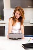 Rothaarigemädchen, das Tabletten-PC in der Küche hält lizenzfreie stockfotos