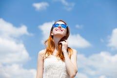 Rothaarigemädchen in der blauen Sonnenbrille Lizenzfreies Stockbild