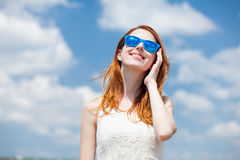 Rothaarigemädchen in der blauen Sonnenbrille Stockfotos