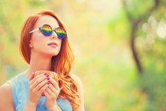 Rothaarigemädchen in der Sonnenbrille mit Regenbogen und mit Schale stockbild