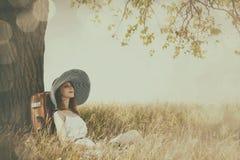 Rothaarigemädchen im Hut, der nahe Baum an der Landschaft sitzt Stockbild