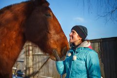Rothaarigemädchen lächelt am roten Pferd an einem sonnigen Wintertag lizenzfreies stockbild