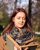 Rothaarigemädchen-Lesebuch im Park Stockbilder