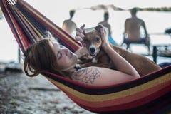 Rothaarigemädchen und ihr Hund, die auf einem Aufenthaltsraum am Strand im Sommer liegen lizenzfreies stockbild