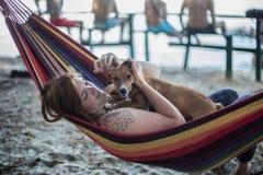 Rothaarigemädchen und ihr Hund, die auf einem Aufenthaltsraum am Strand im Sommer liegen lizenzfreie stockfotografie