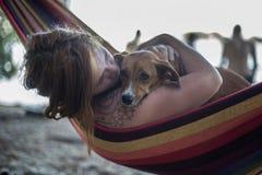 Rothaarigemädchen und ihr Hund, die auf einem Aufenthaltsraum am Strand im Sommer liegen lizenzfreie stockfotos