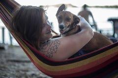 Rothaarigemädchen und ihr Hund, die auf einem Aufenthaltsraum am Strand im Sommer liegen stockbilder