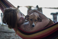 Rothaarigemädchen und ihr Hund, die auf einem Aufenthaltsraum am Strand im Sommer liegen stockfoto
