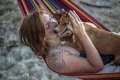 Rothaarigemädchen und ihr Hund, die auf einem Aufenthaltsraum am Strand im Sommer liegen stockfotos