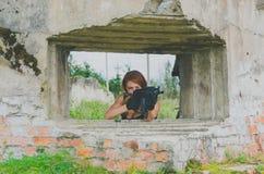 Rothaarigemädchensoldat in der Uniform mit Waffe in der Abdeckung zu zielen Lizenzfreie Stockfotos