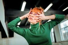 Rothaariger Berufschoreograph mit dem Haarbrötchen, das künstlerisch schaut stockfotos