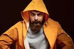 Rothaariger Kerl mit einem Bart und einem Schnurrbart, die in einem grauen T-Shirt und in einer gelben Jacke mit einer Haube gekl lizenzfreie stockfotos