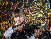 Rothaariger sommersprossiger Junge, der schwarze Violine, Musikkonzept spielt Lizenzfreies Stockfoto