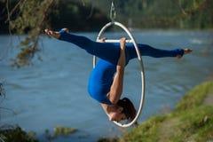 Rothaariger Turner in einer blauen Klage, welche die schwierigen Übungen an der Luft tut, schellen in der Natur Lizenzfreie Stockfotografie