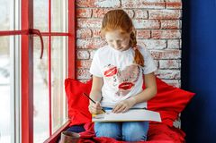 Rothaariges Kind sitzt auf dem Fensterbrett und den Farben Das Konzept stockfoto
