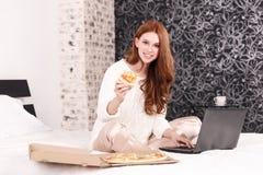 Rothaariges Mädchen auf dem Bett, das an Laptop arbeitet und Pizza isst stockfotos