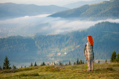 Rothaariges Mädchen auf einem Hügel gegen schöne Berglandschaft Stockfotografie
