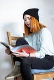 Rothaariges Mädchen, das durch eine Zeitschrift Blätter treibt Stockbild