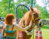 Rothaariges Mädchen, das ein Pferd mit der roten Mähne streichelt stockbild