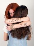 Rothaariges Mädchen, das ich liebe dich ihren Freund in ihren Armen die Aufschrift umarmt Stockfotografie