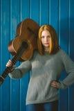 Rothaariges Mädchen, das mit Akustikgitarre steht Stockfoto