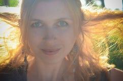 Rothaariges Mädchen in den Ohrringen während der goldenen Zeit Lizenzfreie Stockfotos