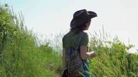 Rothaariges Mädchen in einem Cowboyhut mit einem Rucksack geht auf einen Gebirgspfad stock video