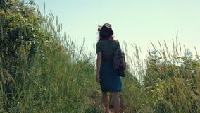 Rothaariges Mädchen in einem Cowboyhut mit einem Rucksack geht auf einen Gebirgspfad stock footage