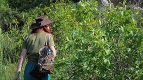 Rothaariges Mädchen in einem Cowboyhut mit einem Rucksack geht auf einen Gebirgspfad stock video footage