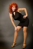 Rothaariges Mädchen in einem schwarzen Kleid Stockbild