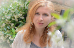 Rothaariges Mädchen gegen die weißen Blumen Lizenzfreies Stockfoto