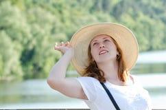 Rothaariges Mädchen im Hut, der gegen Hintergrund von aufwirft, rive Stockbild