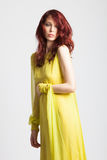 Rothaariges Mädchen im langen eleganten gelben Kleid Stockfotografie