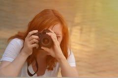 Rothaariges Mädchen macht Fotos auf einer SLR-Kamera, Vorderansicht stockbild
