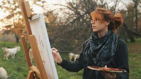 Rothaariges Mädchen mit einem Brötchen, das ein Bild auf einem Gestell in der Natur, eine junge Frau beschäftigt gewesen mit Krea stock video