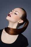 Rothaariges Mädchen mit interessanten Ohrringen, Studioporträt, Schönheit Lizenzfreies Stockfoto