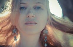 Rothaariges Mädchen mit Sommersprossen in den Ohrringen, Stockbild