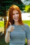 Rothaariges Mädchen mit Sommersprossesich zeigen Daumen und dem Lächeln Lizenzfreie Stockbilder