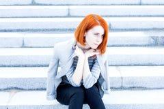 Rothaarigeschönheit mit einer Jacke, die auf der Treppe mit einem durchdachten Blick sitzt Stockfotos