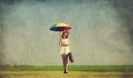 Rothaarigezauberin mit Regenschirm und Koffer am Frühlingsland Stockbild