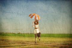 Rothaarigezauberin mit Regenschirm und Koffer am Frühlingsland Stockfotos