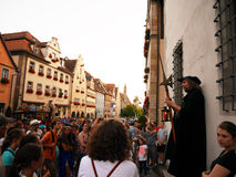 ROTHENBURG O.D.T., GERMANY - July 20, 2016: The Night Watchman. At Marktplatz entertaining and giving informations to tourists who joined his night tour stock photography