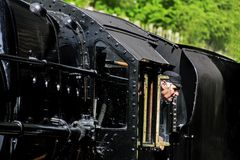 Steam engine driver looking from his Cab to the platform royalty free stock photography