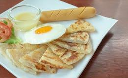 Roti με το γλυκαμένο συμπυκνωμένο γάλα και το τηγανισμένο αυγό, χρυσό delicio Στοκ Εικόνες